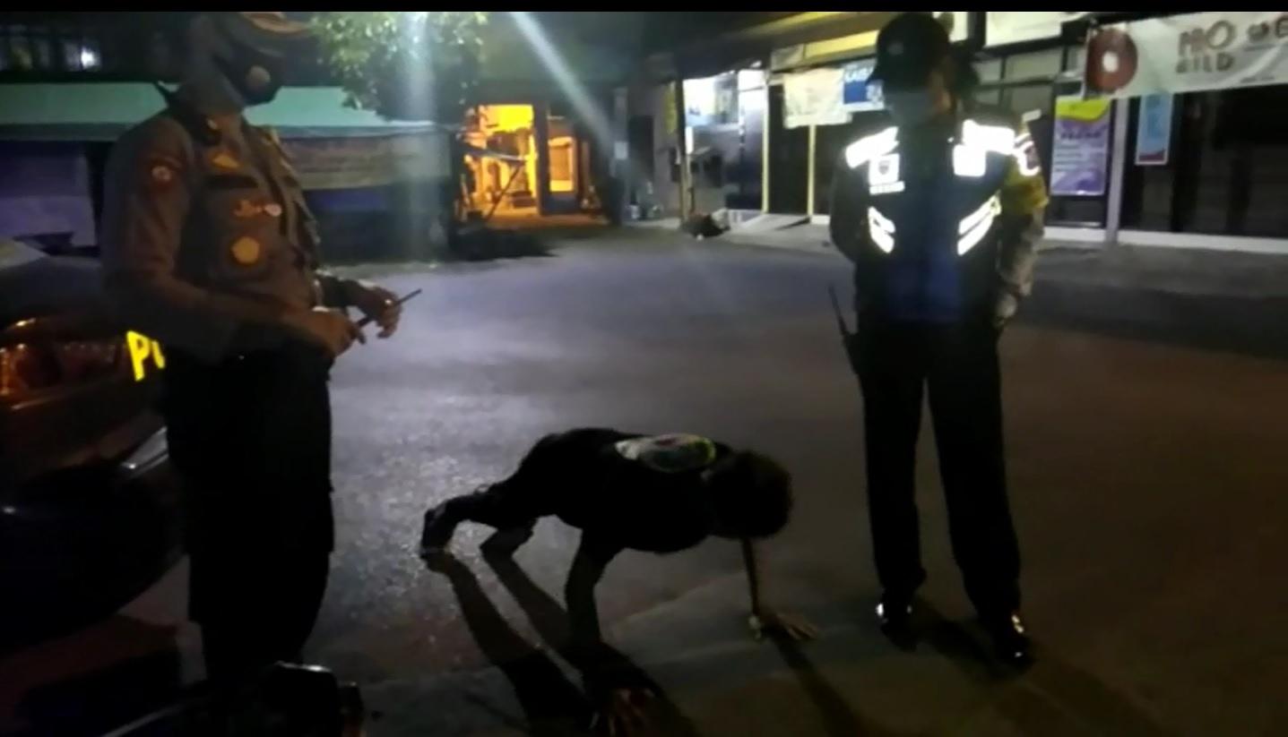 Polisi menghukum salah seorang pemuda lantaran tak mengenakan masker di tempat umum (Foto / Metro TV)