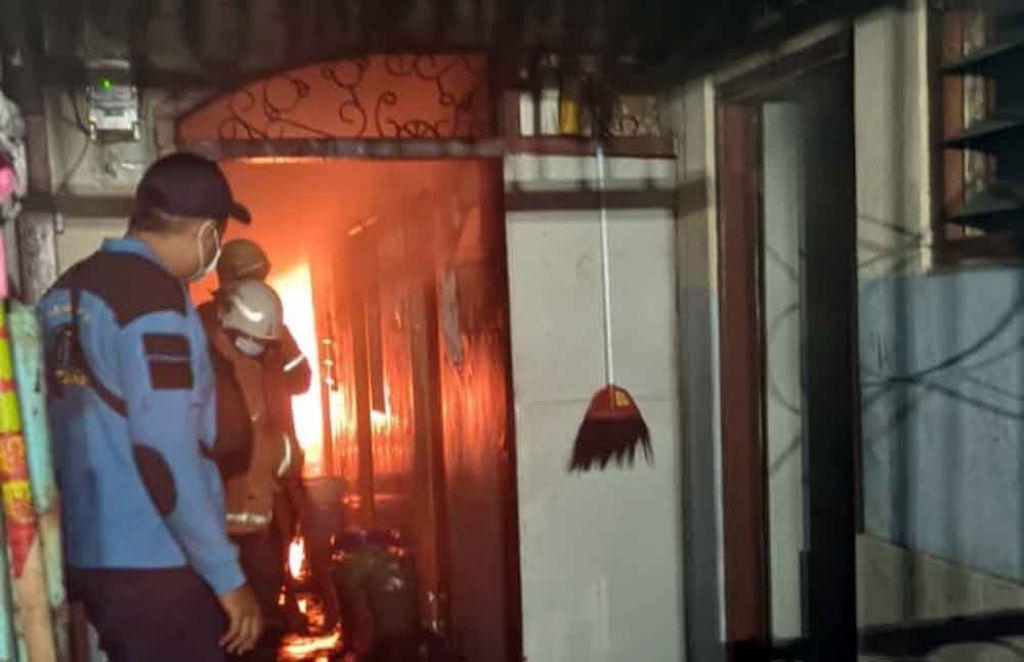 Petugas PMK memadamkan api yang membakar kos di kawasan Surabaya Barat ( Foto / Metro TV)