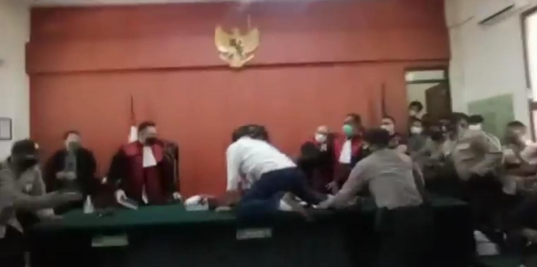 Terdakwa M Yunus melompat ke meja dan mencoba menyerang hakim lantaran tak terima divonis tiga tahun penjara (Foto / Metro TV)