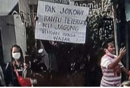 Aksi Suroto saat membentangkan poster ke arah rombongan Presiden Jokowi saat di Blitar. (ist)