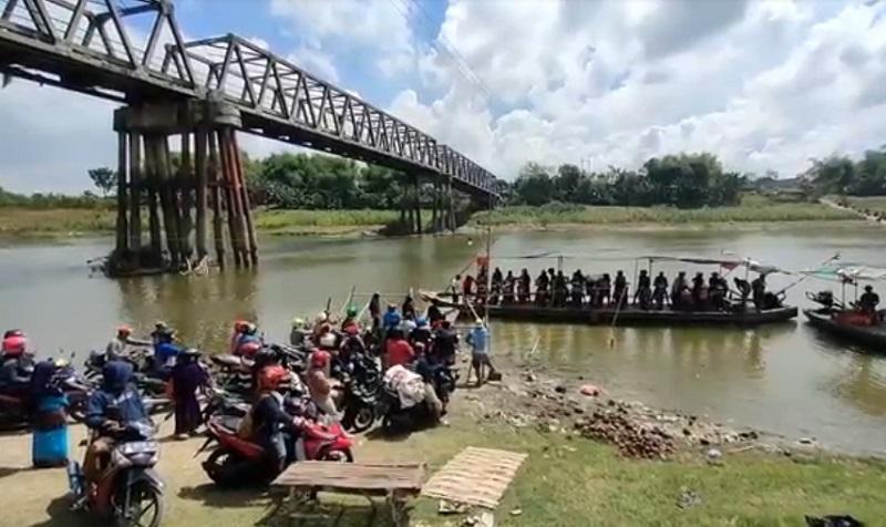 Ratusan pengendara antre menyebrangi bengawan solo dengan perahu setelah jembatan ditutup (Foto / Metro TV)