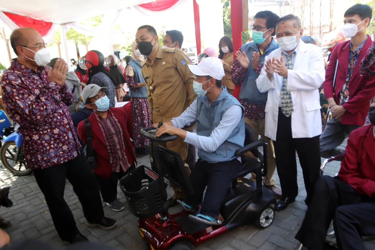 Wali Kota Surabaya, Eri Cahyadi bersama Rektor UM Surabaya, Sukadiono, meninjau inovasi kursi cerdas yang digunakan mahasiswa difabel, Abdul Halim, saat mengikuti vaksinasi lantatur di kampus setempat (Foto / Metro TV)