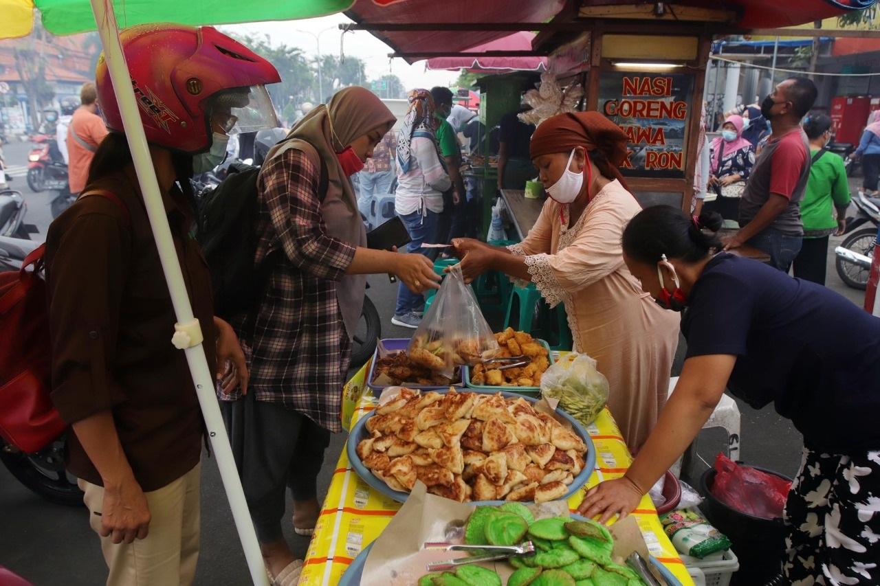Penjual gorengan dan kue basah kerepotan melayani pembeli (Foto / Yuan / Clicks.id)