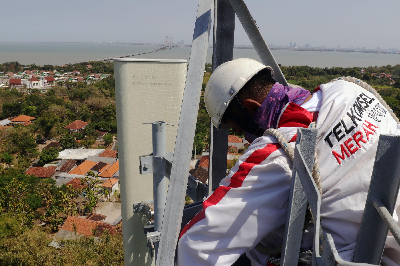 BERI PELAYANAN TERBAIK: Teknisi melakukan perawatan rutin tower Base Transceiver Station (BTS) Telkomsel, yang berada di kawasan Bangkalan, Madura, Rabu (8/9). Jaringan telkomsel 5G diharapkan bisa menghadirkan akses konektivitas digital terdepan yang aka