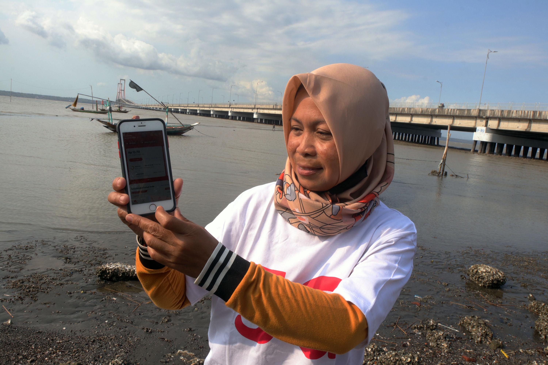 MANFAATKAN APLIKASI: Pelanggan telkomsel di kawasan pesisir pantai Surabaya, menggunakan layanan melalui aplikasi my telkomsel untuk mendukung kegiatan sehari-hari, Rabu (8/9). Jaringan telkomsel 5G diharapkan bisa menghadirkan akses konektivitas digital